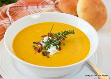 Bowl of Cream of Carrot Soup topped with a dollop of sour cream, bacon bits, and fresh herbs