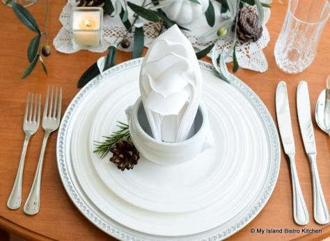 Top-down view of placesetting formed with white dinnerware and silver charger