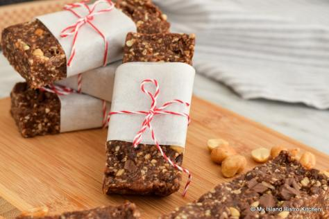 Close-up of Roasted Peanut and Mocha Energy Bars wrapped in parchment paper and tied with red-striped string