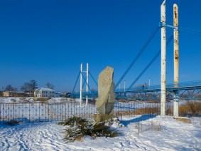 Памятный знак на фоне «Моста Влюбленных» в Изюме