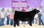 Union Grove's Tori Crisp (far right) showcases her prize-winning Grand Champion Steer at the Wisconsin State Fair among friends, family and event officials. Crisp won the title for the second time in five years (Courtesy of We Know Live Stock)