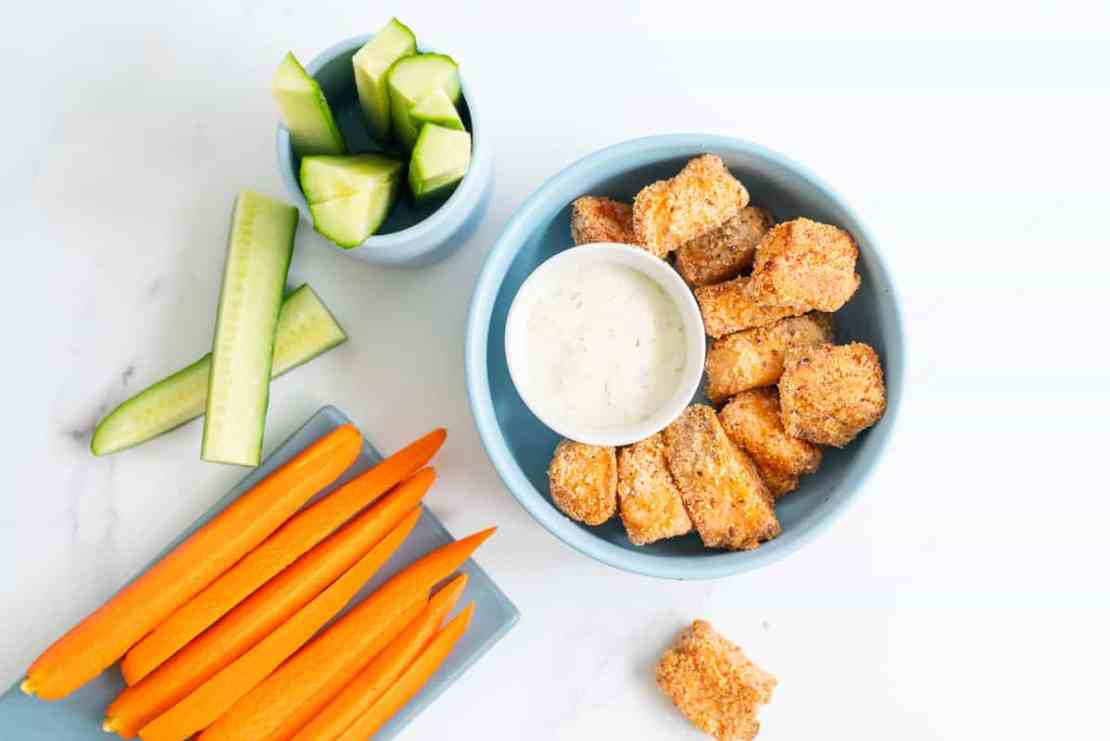 A blue bowl filled with salmon nuggets, alongside cucumber and carrot sticks.