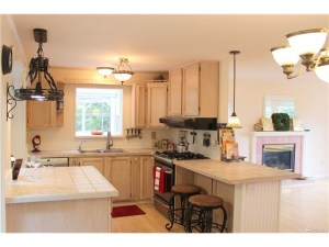 The chef's kitchen has beautiful tile counter tops, light colored cabinets and a gas range.