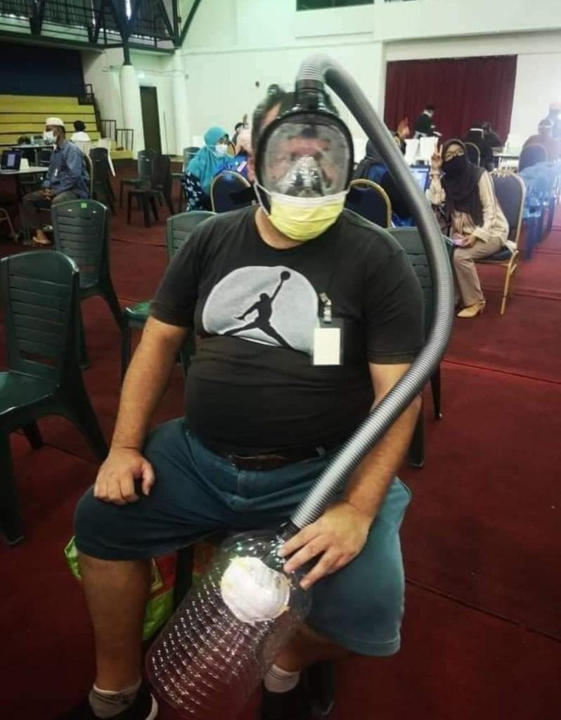 Tindakan lelaki warga asing mengenakan alat pernafasan buatan sendiri di Pusat Pemberian Vaksin