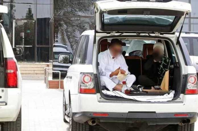 Kuwaiti citizens eat in their cars after the closure of restaurant halls