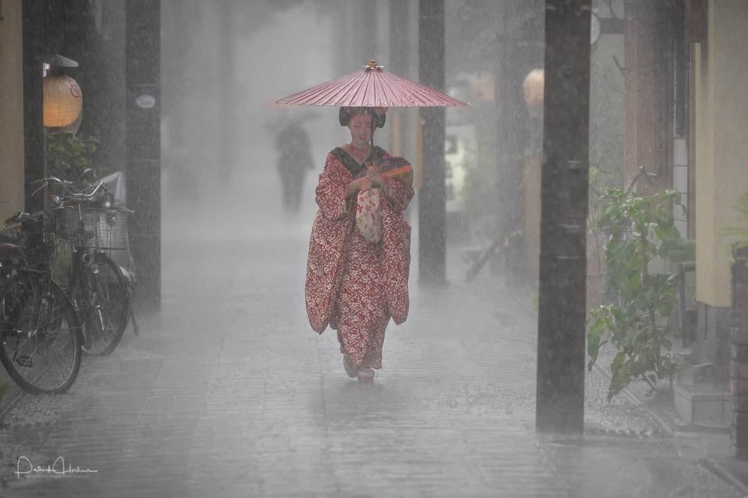 Maiko Kikusana walking under heavy rain, Kyoto