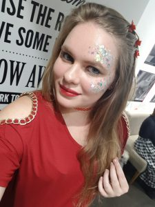 A selfie of Lauren blog writer) looking very 90s with red butterfly clips and glitter face make up.