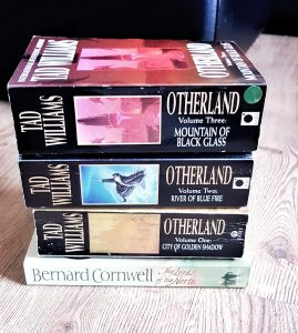 A picture of 4 books on a wooden floor. The books are The Lords of the North by Bernard Cornwell, and the first 3 books in the Otherland series by Tad Williams.