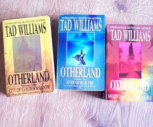 A picture of the first three books in the Otherland series by Tad Williams. The firs is shown with a golden background with a fantasy like city shown in the middle of the cover.This is to match the name City of Golden Shadow. The second Book River of Blue Fire is shown with a azure blue cover with a river running from the city in the middle. The last book Mountain of Black Glass shows a multi-coloured cover with red and yellow being the primary colours. In the centre a black tower stands. This phoeo was taken for My Lavender Tinted World, a sheffield based blog for the Birthday Book Haul post.