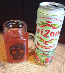 A picture of the Arizona Kiwi Strawberry fruit cocktail as part of the Trying American Sodas blog post. The picture shows the can with strawberries and kiwis along the bottom as well as some of the drink in the can.