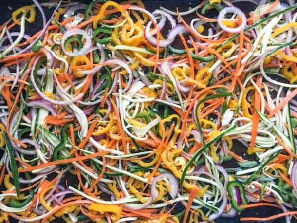 Raw veggie noodles on baking tray.