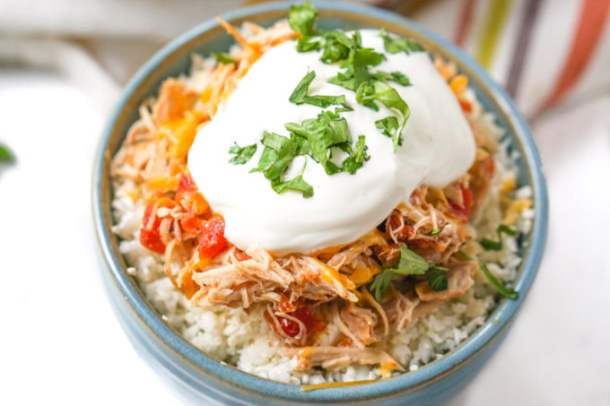 blue bowl with cauliflower rice and slow cooker salsa chicken topped with sour cream and cilantro