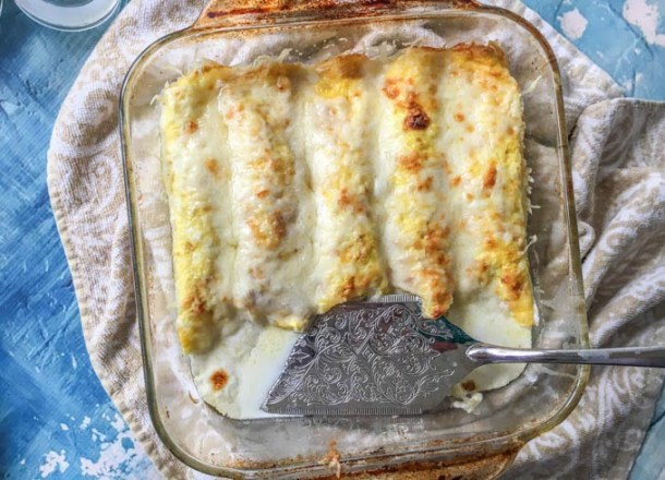 baking dish with low carb chicken crepes and spatula on beige towel