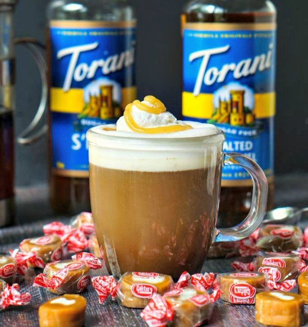 closeup of keto salted caramel cream coffee latte with scatter caramel cream candies and Torani bottles in background