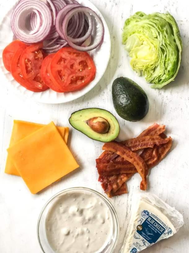 Long photo of burger toppings: bacon, cheese, avocado, blue cheese dressing, salad.