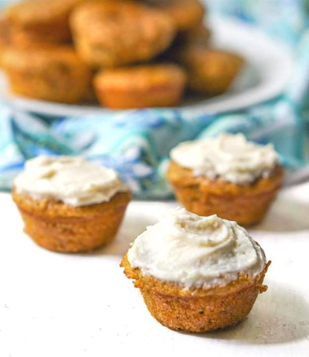mini muffins with cream cheese frosting with plate of plain muffins in background
