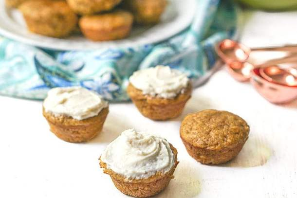mini pumpkin muffins with cream cheese frosting with plateful in background and copper mearsureing spoons