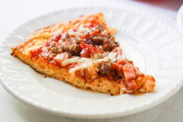 piece of meat lover's low carb pizza on white plate