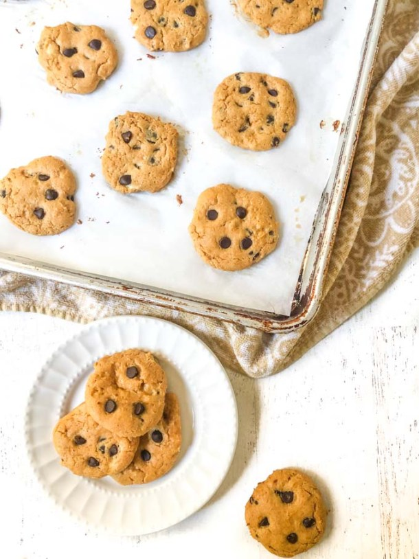 white plate with low carb peanut butter chocolate chip cookies and cookie tray