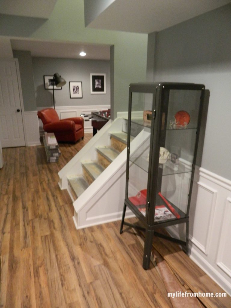 Stairs and sports memorabilia cabinet.