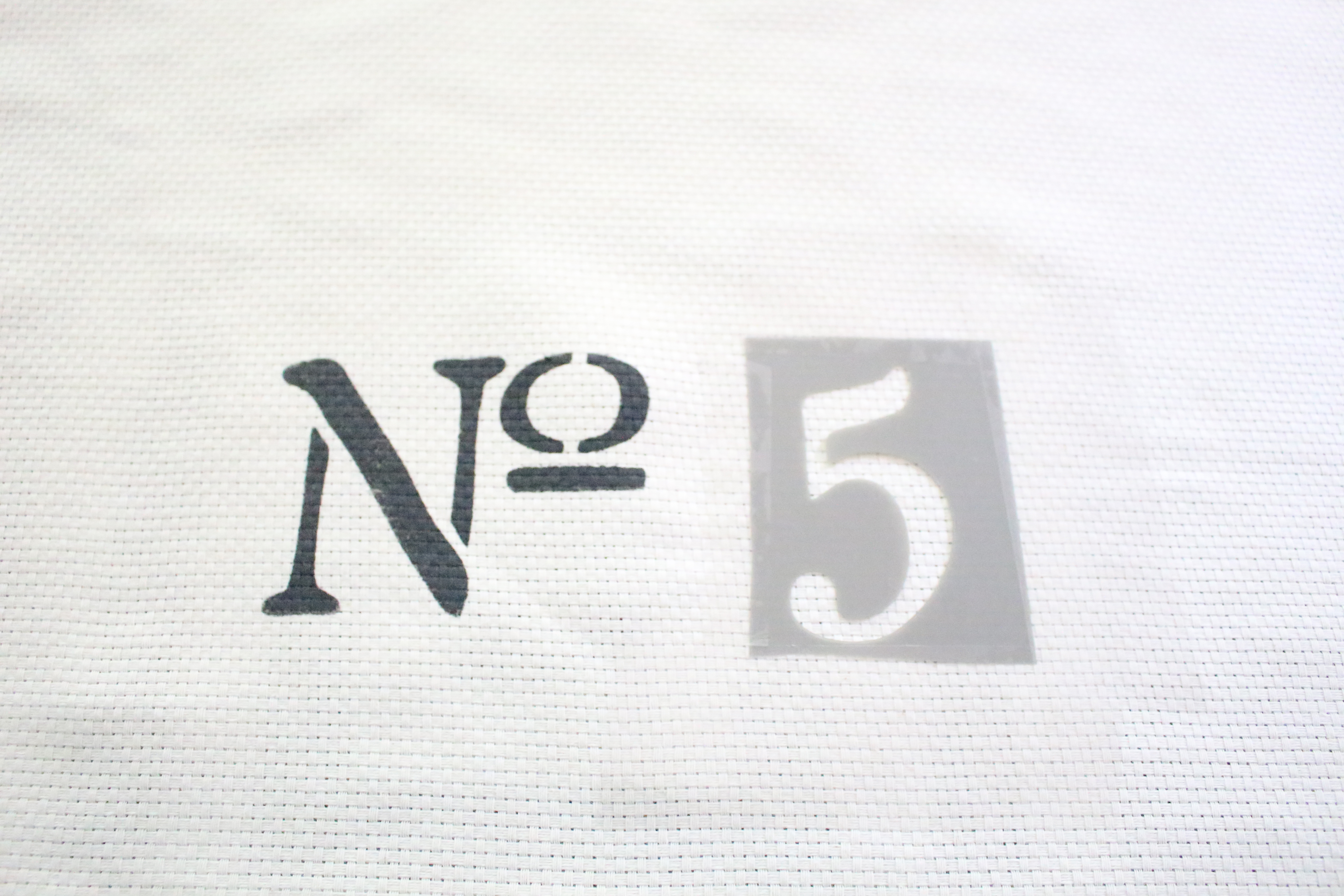 No. 5 Stencil on a Farmhouse Pillow Cover Project by www.whitecottagehomeandliving.com
