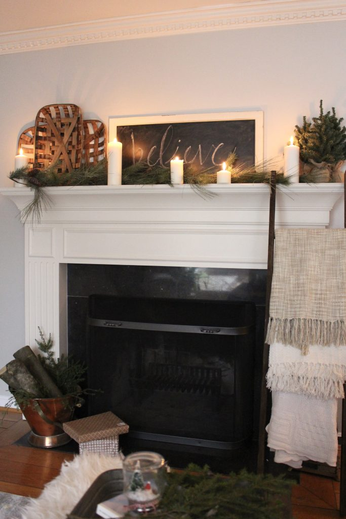 A farmhouse Christmas Mantel dressed in candlelight- home decor- holiday- mantel decor- Do it Yourself- DIY DIY projects- candlelight mantel- living room decorating ideas- room design- rustic home decor- decoration ideas- candlelight and greenery mantel- chalkboard script- winter mantel- candlelight- farmhouse Christmas ideas- decor- tobacco baskets in decor