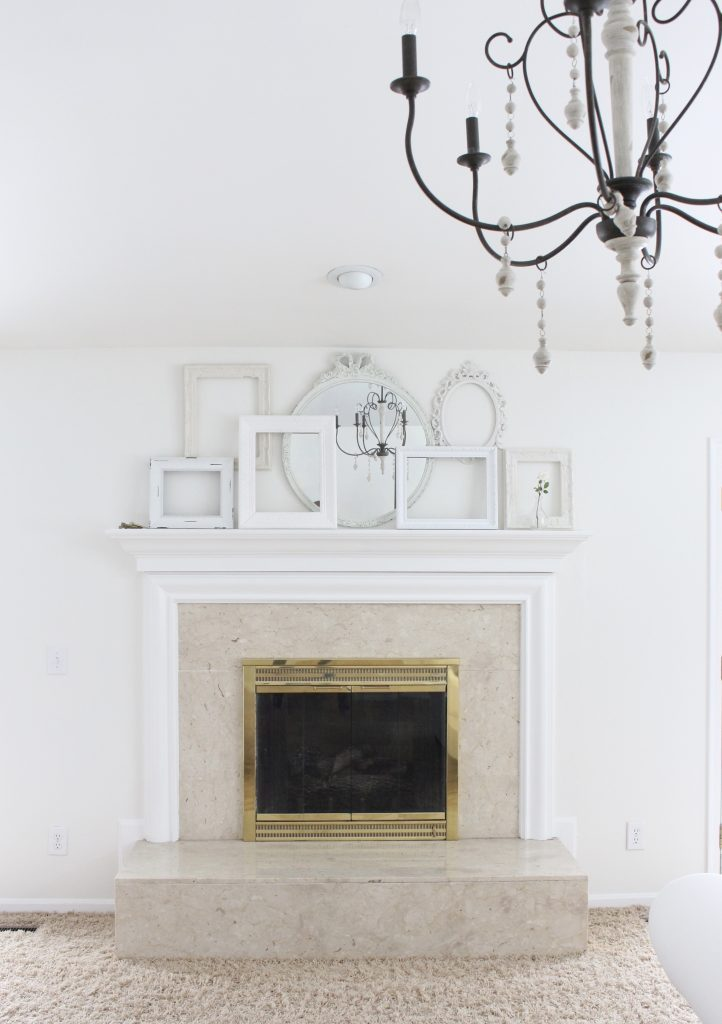 A shabby chic white mantel- layered frames- white mirror- all white decor- romantic design- fireplace decor- mantel decor- home design- decor ideas- mantles- french country style mantel- DIY- Do it Yourself- DIY projects- room design- wall decorating ideas- gallery wall- room decor ideas- decoration ideas- farmhouse style chandelier- french country chandelier