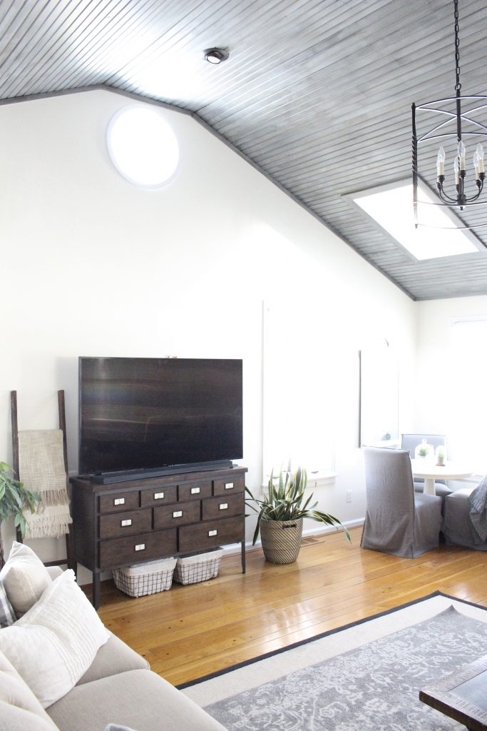 Gray and White Cottage Living Space- farmhouse style room- decor- DIY- weathered wood ceiling treatment- painted ceiling- paint and stain treatment on pine- how to- paint- stain- wood- ceiling- winter decor- room design- home decor- living room decorating ideas- rustic home decor- wall decorating ideas- decoration ideas- room decor ideas- mantel ideas- french county style decor-tv room- decorating with a tv