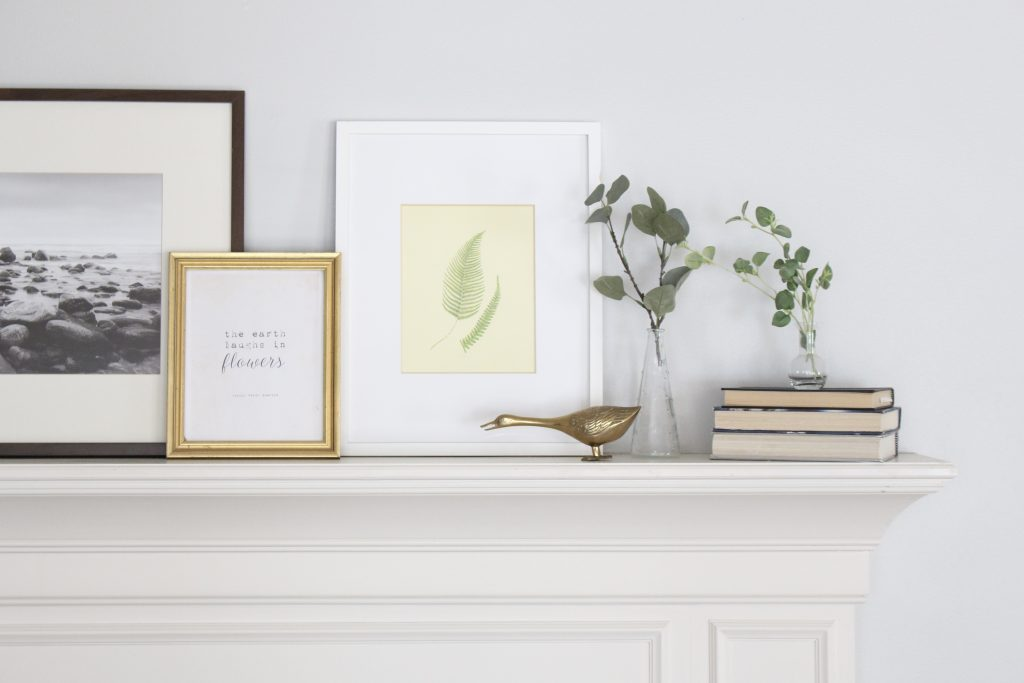spring mantel decor- how to decorate your mantel for spring- mantles- mantel decorating- spring decor- fresh spring ideas- layered frames- wall decorating ideas- home design- diy- diy projects- seasonal mantel decor- brass animals
