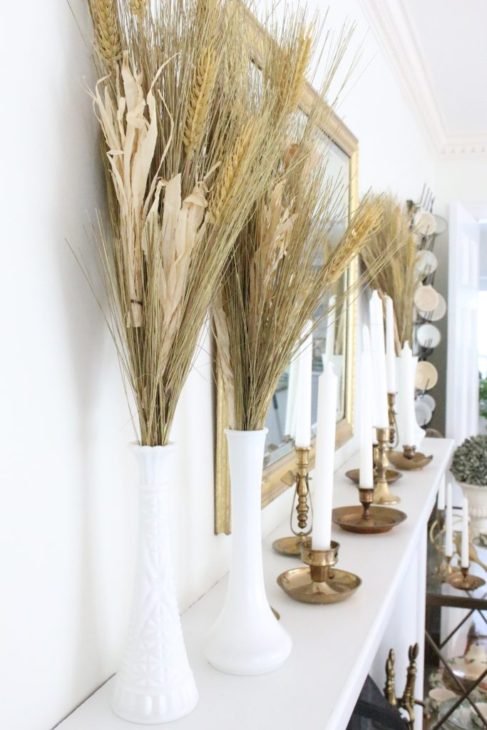 Simple neutral fall colors in our dining room- dining room- fall decor- neutral- living spaces- gold- brass- candlesticks-milk glass- fireplace decor mantel- decorating for fall- seasonal- fall mantel- wheat sheaves- classic- vintage- mantle