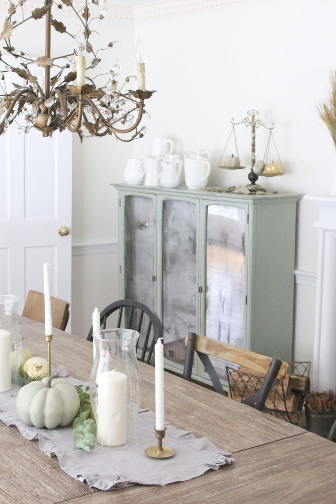 Fall decor- dining room- neutral- white- green- wheat- milk glass- antique brass candlesticks- large dining table- mix and match chairs- decorating a dining room for fall- tablescape- fall table