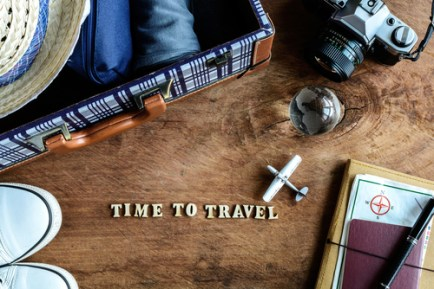 """Outfit of traveler on wooden background with word """"Time to travel"""""""