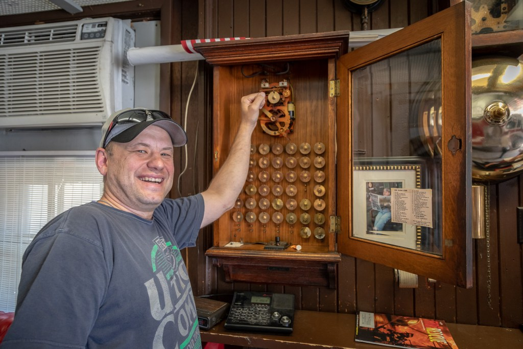 Photo by Dave Warner - Scott Kinville shows off the old fire alarm system which is still in use to this day.