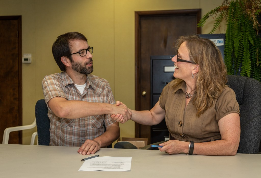 Photo by Dave Warner - Tolga Morawski (left) with the Greater Mohawk Valley Land Bank shakes hands after the signing of the Memorandum of Understanding with Judy Wolf, President of Main Street First.