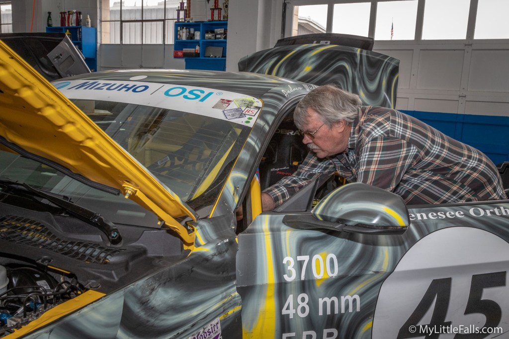 Photo by Dave Warner - Mike Evans spends a minute checking out the interior of one of the race cars in his shop.