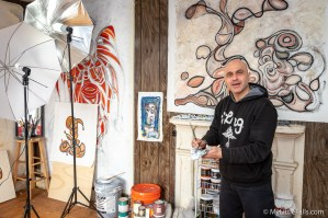 Photo by Dave Warner - Artist Elias Saifan cleans one of his brushes after working on a recently completed canvas.