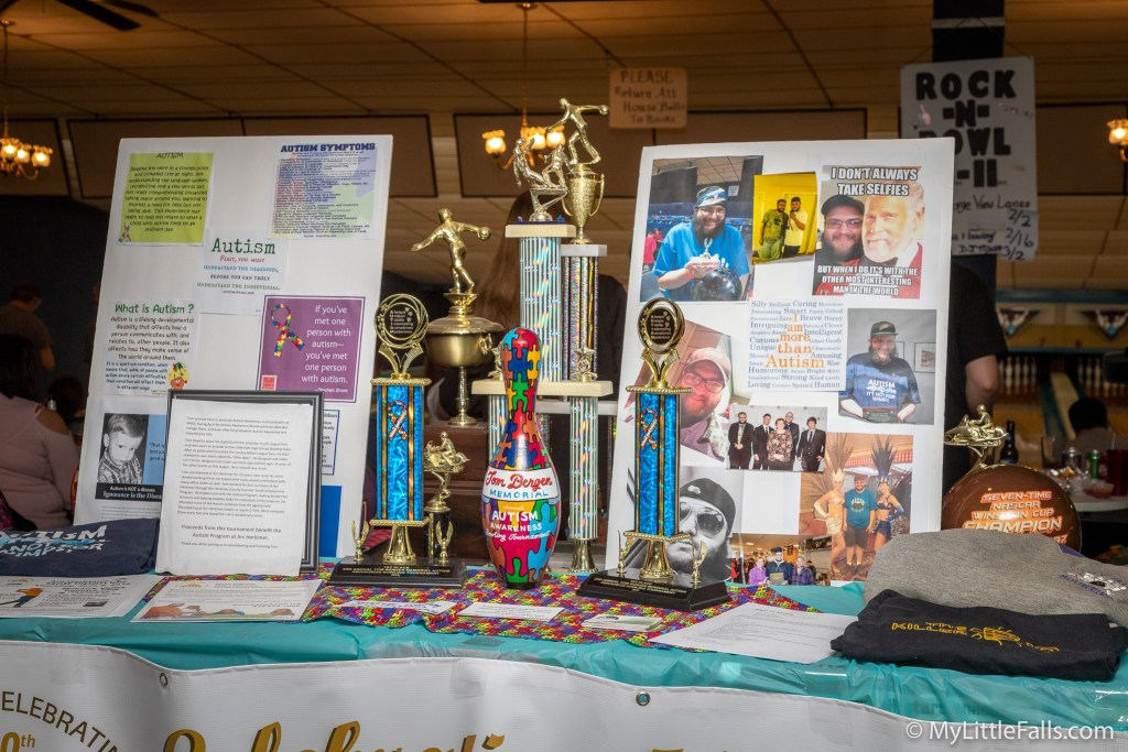 Photo by Dave Warner - volunteers set up a display with pictures of Tom Bergen and an explanation of symptoms during the third annual Tom Bergen Memorial Autism Awareness Bowling Tournament.