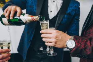 men in tuxedos pouring sparkling wine