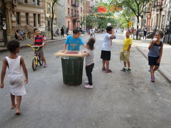 Jeo (in blue) plays checkers on a garbage can (159th).