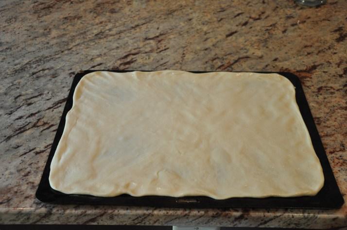 homemade dough spread on baking sheet