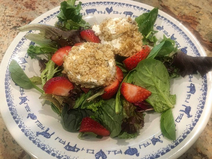 Place 2 slices of goat cheese over salad greens in each bowl.