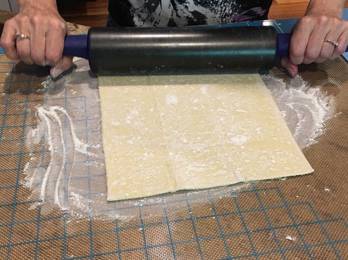 If using frozen puff pastry allow pastry to thaw at room temperature for 30 minutes.  Preheat oven to 400 degrees Fahrenheit Sprinkle a small amount of flour on a clean workspace and place puff pastry flat. Using a rolling pin, gently roll dough until fold lines are gone