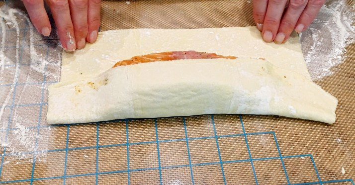 Fold puff pastry over salmon overlapping one side over the other