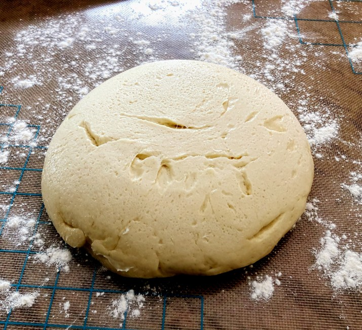 when the dough has doubled in size, place it on your work surface and sprinkle with flour.
