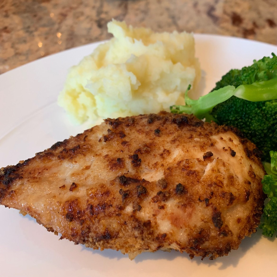 air fryer buttermilk ranch chicken on a dish with mashed potatoes and broccoli