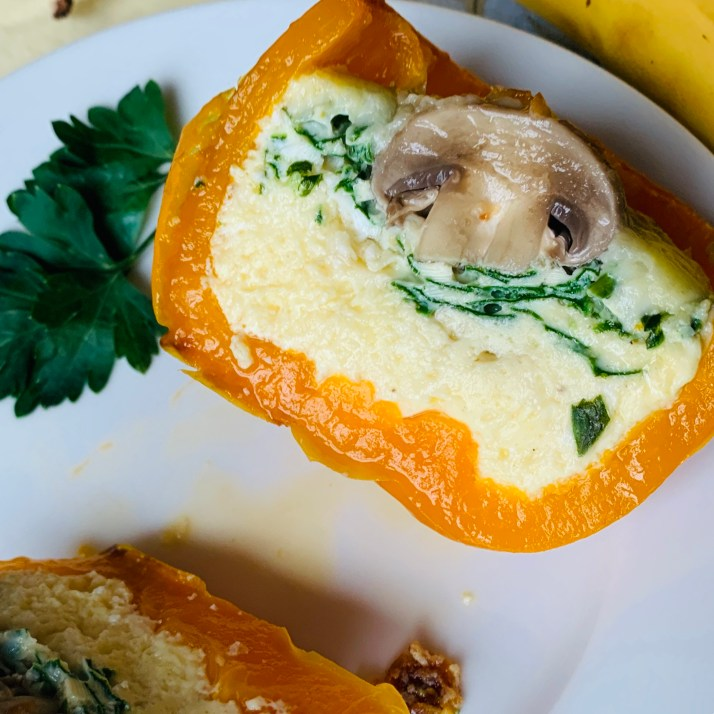 egg-stuffed breakfast pepper with spinach and a mushroom perfectly placed in the center.