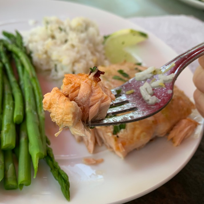 A fork with a piece of grilled salmon, sided with basmati rice and asparagus.