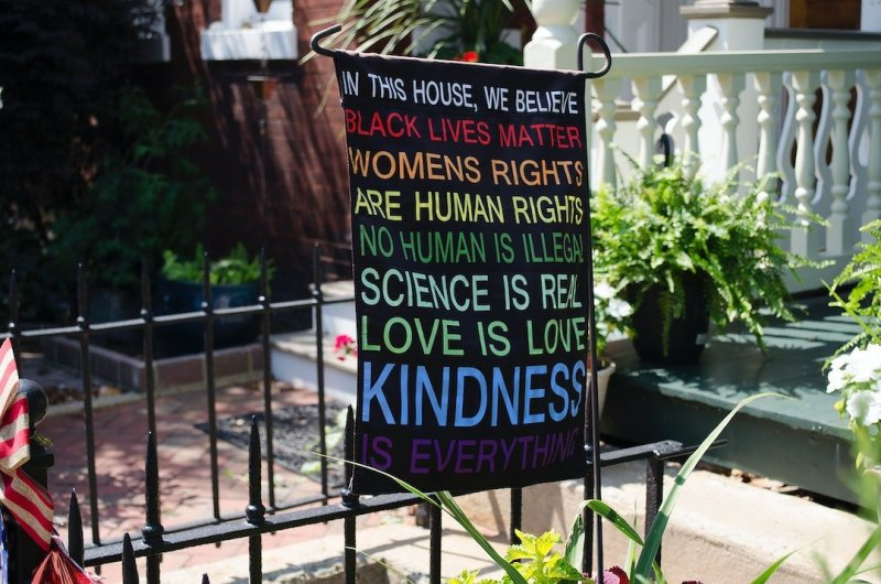 """Photo of a flag that reads: """"In this house, we believe Black Lives Matter, Women's Rights Are Human Rights, No Human Is Illegal, Science is Real, Love is Love, Kindness is Everything."""