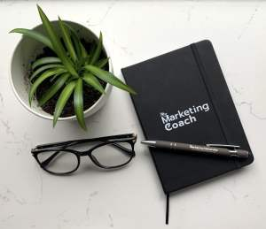 My Marketing Coach journal with My Marketing University pen alongside glasses and a small plant