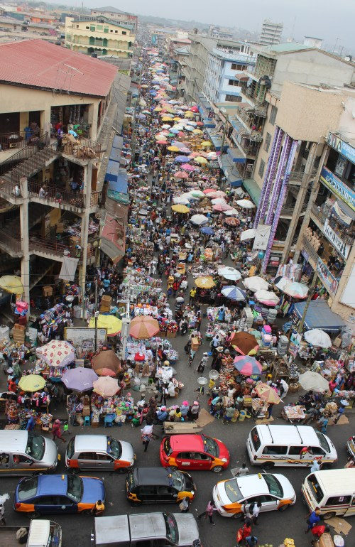 A view down one of the streets of Makola Market Accra with lots of umbrellas, vendors and pedestrians